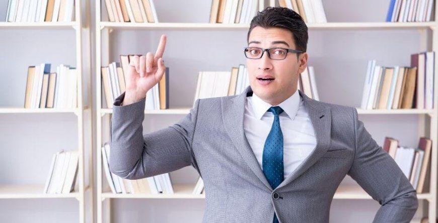 negativado-indevidamente homem vestido de terno aponta para vários livros de direito