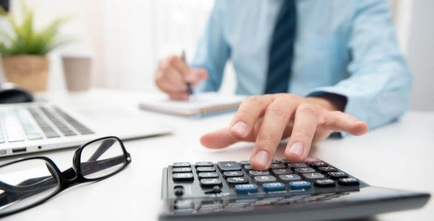 imposto-de-renda homem faz cálculo na calculadora para descobrir quanto terá de pagar de imposto de renda