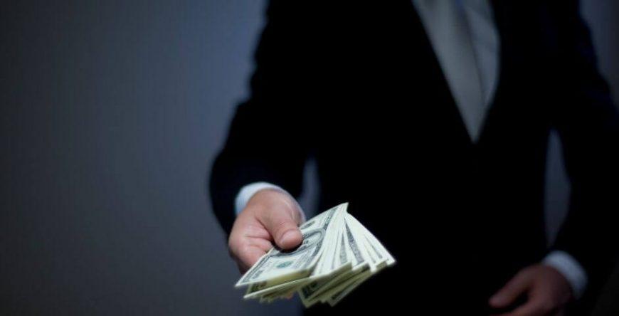 declaracao-imposto-de-renda homem segurando dinheiro na mão