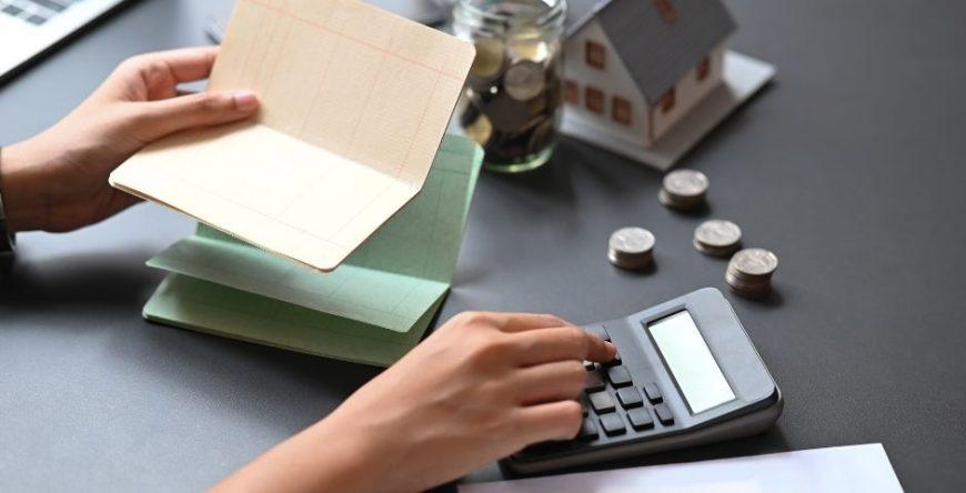 homem ou mulher faz cálculo na calculadora para descobrir se é melhor pagar a fatura do cartão de crédito pelo rotativo ou parcelamento